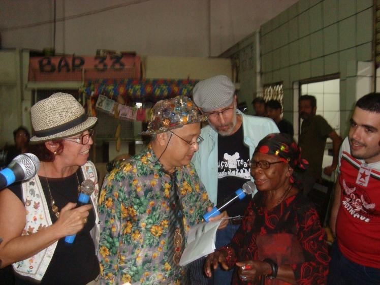 Veio Mangaba, ao centro, entrevista dona Maria José , torcedora-ícone do Sport, num Banco de Feira no Mercado da Encruzilhada, em agosto de 2010. Euzinha e Ruy Sarinho, produtor e diretor do programa, acompanhamos - Foto: Ilná Dantas