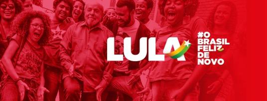 A logo aplicada sobre a foto de Lula numa sarrada com jovens na Bahia, durante a Caravana Lula Pelo Brasil/Nordeste, ano passado. Um filtro vermelho foi aplicado na foto, que é de Ricardo Stuckert, naturalmentd